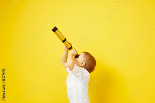 Side view of a child looking through a telescope on a yellow background Fototapeta