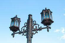 Old Fashioned Lamp. Vintage Street Lamp On A Blue Sky Background. Street Lamp On The Background Of The Blue Sky. Antique Wrought Iron Lantern With Glass Inserts On The Background Of The Blue Sky.