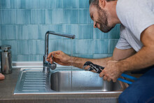 Fix A Leak. Close Up Shot Of Professional Repairman Using Pipe Wrench While Examining And Fixing Faucet In The Kitchen