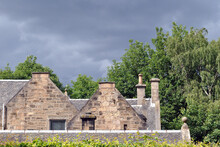 Roof Line Of Old Stone House & Trees Against  Grey Stormy Sky