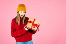 Young Smiling Happy Hipster Girl With Baces Holding Present Boxes Celebrating New Year, Wearing Red Knitted Sweater And Yellow Hat. Christmas Gifts And Winter Fashion Trend.