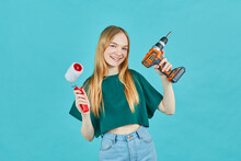 Beautiful Girl With An Electric Screwdriver And An Paint Roller On Blue Background. Instruments Accessories For Renovation Apartment Room. Repair Home Concept.