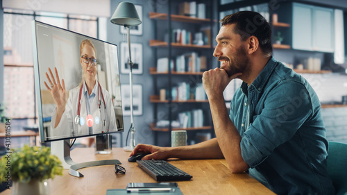 Handsome Caucasian Male is Making a Video Call to His Medical Consultant on Desktop Computer at Home Living Room while Sitting at Table. Man Working From Home and Talking to a Doctor Over the Internet