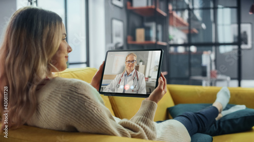 Fototapeta Close Up of a Female Chatting in a Video Call with Her Female Family Doctor on Digital Tablet from Living Room. Ill-Feeling Woman Making a Call from Home with Physician Over the Internet. obraz