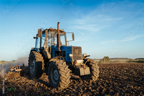 Obraz na plátně The tractor plows the land. Agriculture image