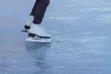 A Child In White Skates Clumsily Rides In Winter On The Ice Of A River Or Lake