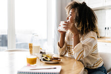 The Side View Of A Smiling Woman Holding A Cup In Her Hands And Looking Out The Window While Sitting In The Kitchen