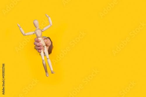 Obraz Mano de hombre sujetando la figura de madera modelo maniquí a travéz de un agujero de un papel amarillo liso y aislado. Vista de frente. Copy space - fototapety do salonu