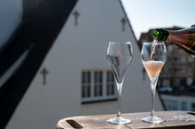 Pouring Of Rose Champagne Sparkling Wine In Flute Glasses On Outdoor Terrace In France