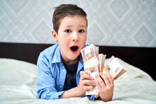 A Little Boy Holds Five-thousand-dollar Bills In His Hands And Is Happy.