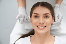 Top View Portrait Of Smiling Beautiful Young Woman In White Shirt Doing Procedure For Improvements Face Skin. Concept Of Special Cosmetics Injection For Anti-aging In Beauty Salon.