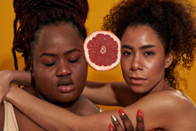 Close Up Portrait Of Two Serious Young African American Women Holding Half Of Juicy Grapefruit Between Them, Posing Together Isolated Over Orange Background