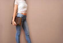 Woman In Blue Jeans And Short White Shirt Stay Next To The Wall With Large Leather Book In Hand