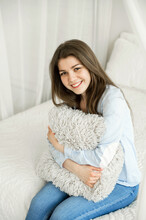 Young Girl With A Pillow Sits On The Bed In Her Room. Happy Student Hugs A Pillow. Man On The Bed. Home Relaxation