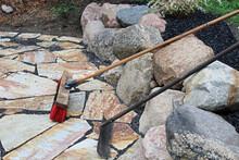 A Rake And Broom Used On Patio Stones
