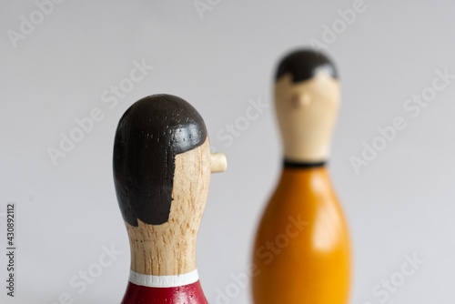 Fotografija Selective focus shot of a wooden skittle with a face isolated on a white backgro