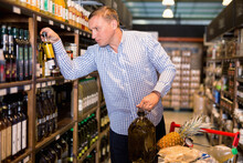 Happy Cheerful Smiling Male Customer Choosing Olive Oil In Average Food Shop