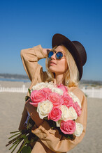 Woman With Flowers At The Beach
