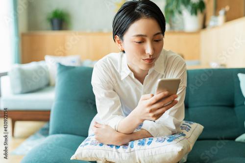 Obraz リビングでスマートフォンを見る女性 - fototapety do salonu