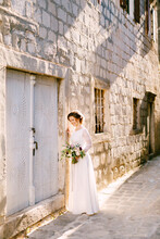 Lovely Bride Stands Near A Brick Wall. She Smiles And Holds In Her Hands A Bouquet Of Beautiful Flowers