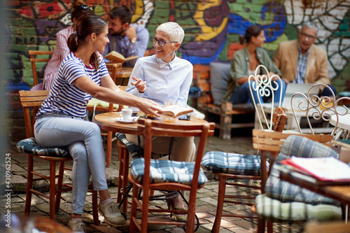 An older woman and her young female friend talking about a book while they have a drink in the bar. Leisure, bar, friendship, outdoor