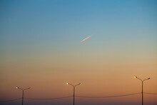 Evening Sky At Sunset With A Flying Plane. Travel, Summer And Relaxation Concept. Beautiful Summer Evening Photography