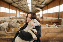 Young Happy Woman On A Sheep Farm Hugging With Sheep