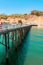 Top Photo Of A Pier On Malibu Beach, California. People Walking On The Weekend. Los Angeles, USA - 15 Apr 2021