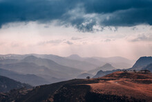 A Beautiful View Of The Mountains With A Tonal Perspective, A Pre-storm Sky With Sun Rays Through The Clouds, A Mountain Serpentine And A Lone Tree On The Top Of The Mountain