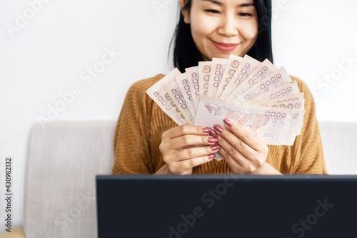 Fotografia, Obraz happy Asian business woman hand holding Thai baht banknotes setting on sofa , su