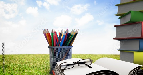 Composition of glasses on opened book, stack of books and container of colour pencils over sky