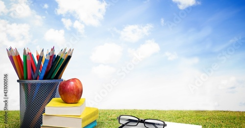 Composition of glasses on book, stack of books, apple and colour pencils over grass and sky