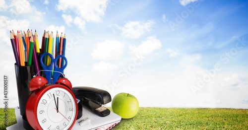 Composition of alarm clock, books, apple and container of colour pencils over grass and sky