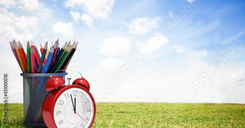 Composition of alarm clock and container of colour pencils over grass and sky
