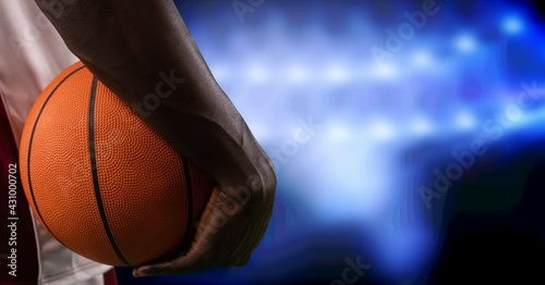 Composition of midsection of basketball player holding basketball over blue spotlights