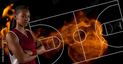 Composition of female basketball player over basketball court and flames