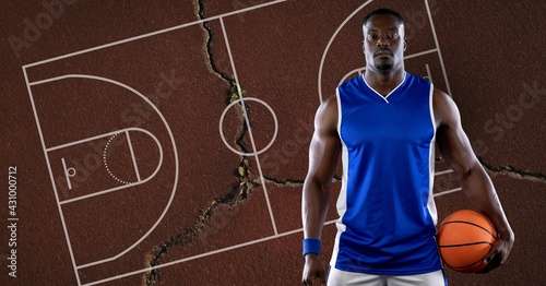 Composition of basketball player holding ball over basketball court and cracked surface