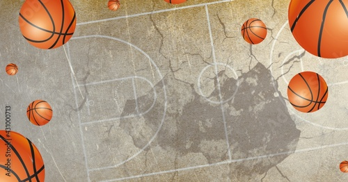 Composition of multiple basketballs in air over basketball court cracked distressed surface