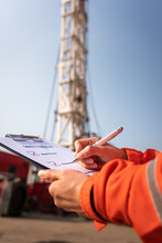 A Safety Office Is Writing On Checklist Document During Perform Safety Audit And Risk Verification At Drilling Site Operation With Blurred Background Of Mount Truck Rig. Selective Focus At Hand.