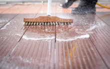 Detail Of A Man With A Scrubbing Brush And A Water Hose Making Spring Cleaning Of A Wooden Terrace Floor