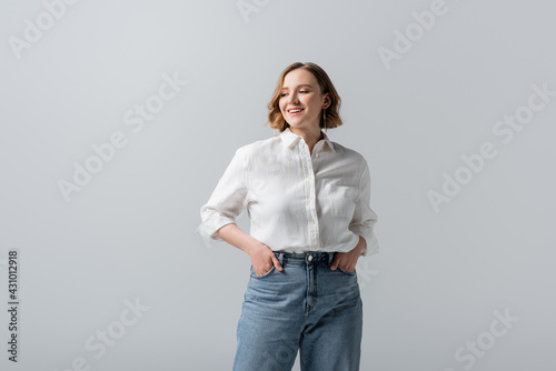 Photo smiling overweight young woman in jeans posing with hands in pockets isolated on