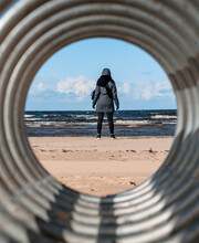 Silhouette Of Human In Winter Clothes, Blue Sea, Sandy Beach And Clouds In The Sky Through The Round Hole Of The Metal Construction