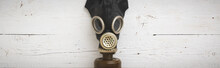 Closeup Of A Vintage Black Rubber Gas Mask On A White Wooden Background. Front View Of A Gas Mask With A Filter. Wide View