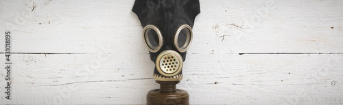 Fotografie, Obraz Closeup of a vintage black rubber gas mask on a white wooden background