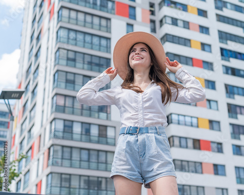 Obraz Happy caucasian young woman in a hat and shorts walks on a city street on a hot summer day - fototapety do salonu