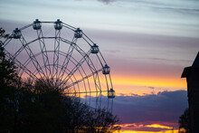 Ferris Wheel Cabins On The Background Of A Beautiful Sunset. Clouds Painted In Different Colors By The Setting Sun. Landscape In The Golden Hour