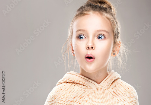 The child is a beautiful girl with wide eyes, look away in surprise. Baby in a knitted sweatshirt . Children's products , clothing and accessories . Expressive facial emotions