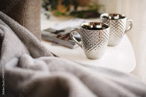 Obraz Silver mugs and fluffy, warm blanket - fototapety do salonu