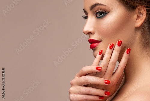 Obraz na plátně Beautiful woman showing red lips and   manicure nails
