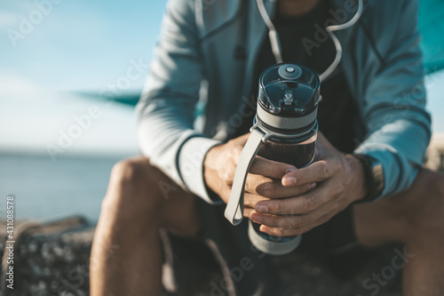 sport man sitting after running and holding water bottle drink. Sport thirsty and resting after exercise. - fototapety na wymiar